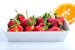 Une pile des oranges avec des fraises Images libres de droits