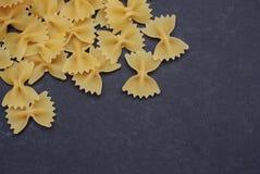 Une pile des pâtes de Farfalle d'isolement sur le coin sur le fond noir Copiez la pâte pour le texte photographie stock libre de droits