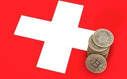 Une pile des pièces de monnaie de Bitcoin se tient sur le drapeau de la Suisse 3d rendent Images stock