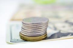 Une pile des PIÈCES DE MONNAIE sur les dollars image stock