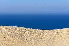 Une pile du sable sur une plage contre la mer et le ciel Photographie stock libre de droits