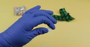 Une pilule blanche ronde à disposition habillée dans le gant médical stérile en caoutchouc banque de vidéos
