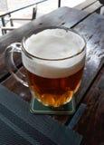 Une pinte de bière sur un Tableau en bois photographie stock