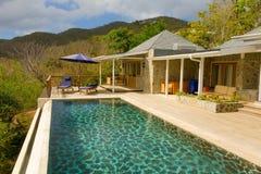 Une piscine d'infini donnant sur une baie dans les îles au vent image stock
