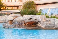 Une piscine de pierre verse l'eau hors de elle photos stock