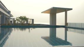 Une piscine luxueuse sur le toit de la maison avec une vue de mer Sur le coucher du soleil 4k, mouvement lent, ?clat solaire sur  banque de vidéos