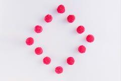 Une place et un losange des sucreries et de la gelée roses et rouges sur le petit morceau Image libre de droits