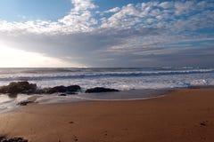 Une plage étonnante avec des roches, des vagues et le sable d'or photographie stock