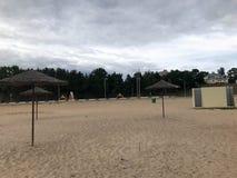 Une plage abandonnée vide en mauvais temps, automne froid pendant la morte-saison avec les parasols couverts de chaume contre le  Photographie stock