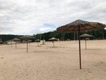 Une plage abandonnée vide en mauvais temps, automne froid pendant la morte-saison avec les parasols couverts de chaume contre le  Photographie stock libre de droits