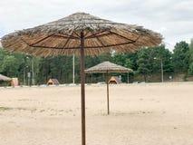Une plage abandonnée vide en mauvais temps, automne froid pendant la morte-saison avec les parasols couverts de chaume contre le  Photo stock
