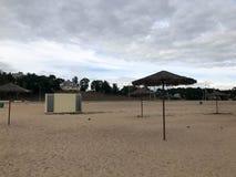 Une plage abandonnée vide en mauvais temps, automne froid pendant la morte-saison avec les parasols couverts de chaume contre le  Photos stock