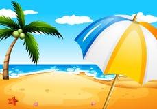 Une plage avec un parapluie Image libre de droits