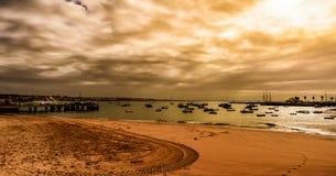 Une plage de couleur avec de petits bateaux sur l'horizon Photographie stock libre de droits