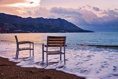Une plage de sable avec des canapés du soleil au lever de soleil Photos stock