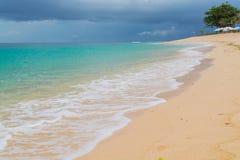 Une plage tropicale avec des nuages de tempête Photos stock