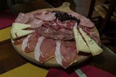 Une planche à découper en bois avec les produits gastronomiques typiques d'Urbino photos stock