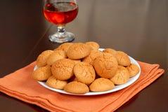 Une plaque des biscuits croquants d'Amaretti avec le verre ballon d'Amaretto en Ba photographie stock libre de droits