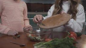 Une plus jeune fille aide la salade végétale coocking de fille plus âgée pour le petit déjeuner se reposant à une petite table da clips vidéos