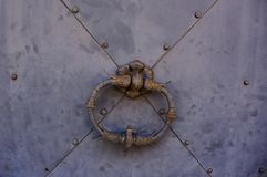 Une poignée de porte en métal sur une porte grise en métal photos stock