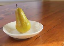 Une poire solitaire dans une cuvette blanche Photographie stock