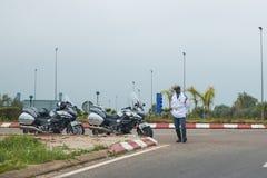 Une police se tient sur la route avec la grande moto deux Photographie stock