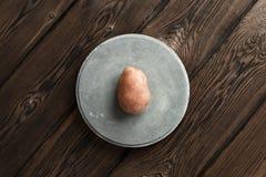 Une pomme de terre crue fraîche sur la tuile en béton sur le fond foncé de conseil en bois photo libre de droits