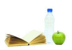 Une pomme et une eau de livre Photo stock