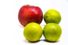 Une pomme rouge et chaux trois verte Photographie stock libre de droits