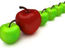 Une pomme rouge parmi la rangée des pommes vertes Image stock