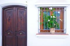 Une porte et une fenêtre décorées des fleurs Image stock