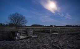 Une porte ouverte sur un champ pendant la nuit avec une pleine lune Photographie stock libre de droits
