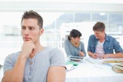 Une position d'étudiant et la pensée en tant que ses amis travaillent derrière lui Image stock