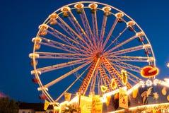Une position de grande roue illuminée contre le ciel de soirée Photographie stock libre de droits
