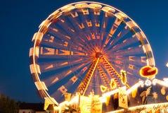Une position de grande roue illuminée contre le ciel de soirée Image stock