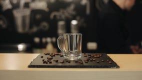 Une position en verre vide de tasse sur le compteur de barre avec des grains de café banque de vidéos