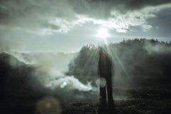 Une position silhouettée à capuchon solitaire de figure dehors Dans un paysage de tabagisme brûlé r Avec la lentille délibérée f image stock