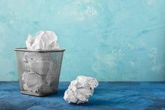 Une poubelle avec des papiers, un morceau se trouve à côté de elle Beau fond peu commun avec l'endroit pour le texte Photos stock