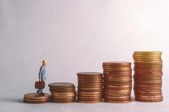 Une poupée du ` s d'homme d'affaires se tient sur des pièces de monnaie pour des pièces de monnaie de collection photographie stock