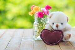 Une poupée et un coeur d'ours se reposent avec des fleurs dans le vase sur le tabl en bois Images stock