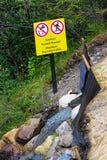 Une précaution a traité des eaux d'égout avertissant près de l'eau courante Photo libre de droits
