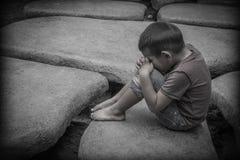 Une prière se reposante de jeune garçon asiatique sur les roches Photographie stock