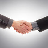 Une prise de contact entre deux hommes d'affaires sur le gris Photographie stock libre de droits