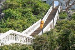 Une promenade de moine en bas des escaliers dans le temple, Thaïlande Images stock