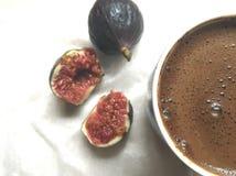 Une pulpe des figues fraîches et tasse de café sur un tissu blanc photos stock