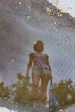 Une réflexion d'une jeune fille dans a après pluie Photos stock