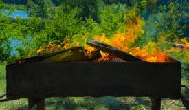 Une rôtissoire avec des charbons brûlants et une flamme rouge images stock