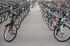 Une rangée d'un grand nombre de bicyclettes avec des roues sur le squa de ville Photos stock