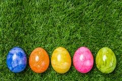 Une rangée de cinq oeufs de pâques colorés sur l'herbe verte Photos libres de droits