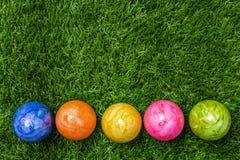 Une rangée de cinq oeufs de pâques colorés sur l'herbe verte Image libre de droits